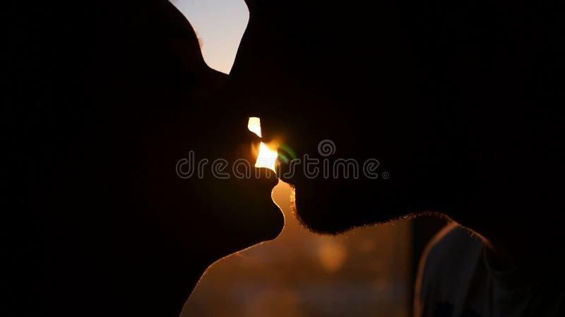 Liebevoller Paarmann und -frau küssen leidenschaftlich bei dem Sonnenuntergang und fangen den Effekt der Linse von der Sonne HD stockfotografie