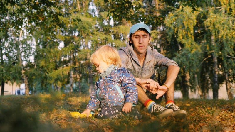 Liebevoller Vater, der mit seinem Sohn auf dem Gras sitzt stockbild