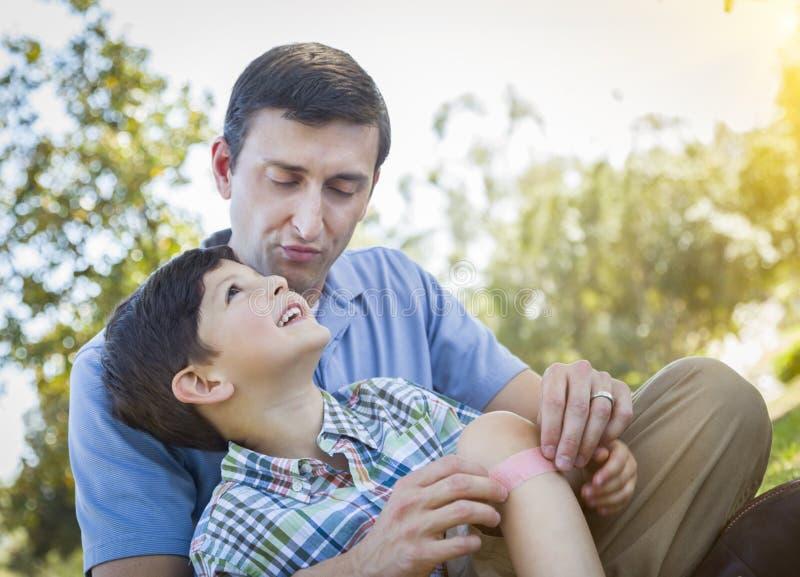 Liebevoller Vater Puts Bandage auf Knie des jungen Sohns stockfoto