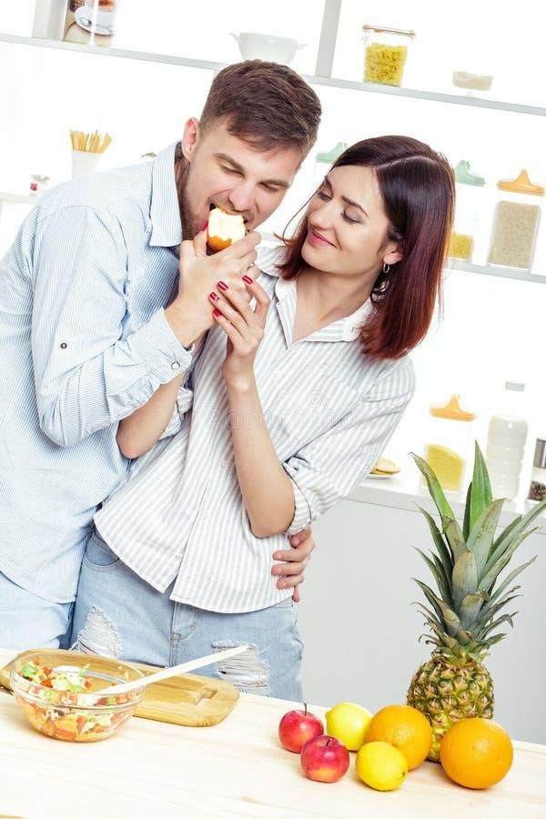 Liebevolles glückliches Paar, das Apfel in der Küche isst lizenzfreies stockfoto