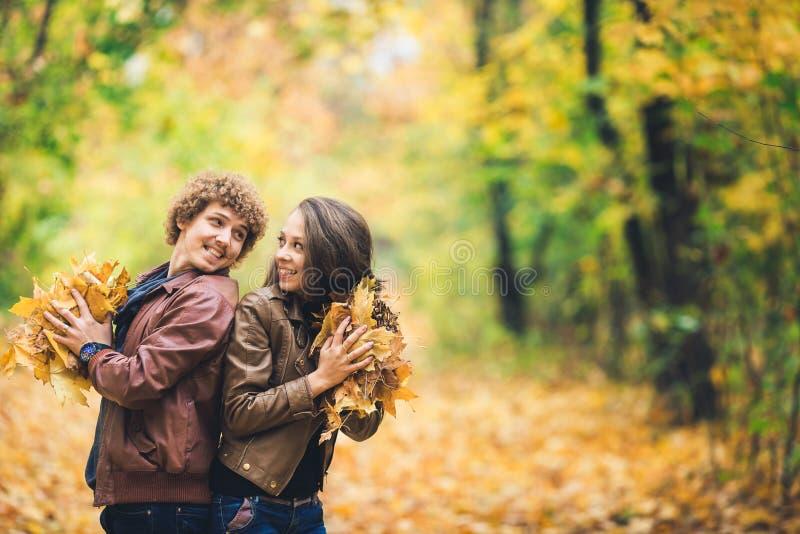 Liebevolles glückliches Paar im Herbst im Park, der Herbstahornblätter in den Händen hält stockbild