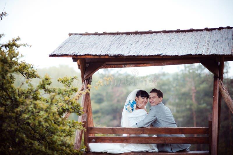 Liebevolles Hochzeitspaar sitzt auf einer Bank stockfoto