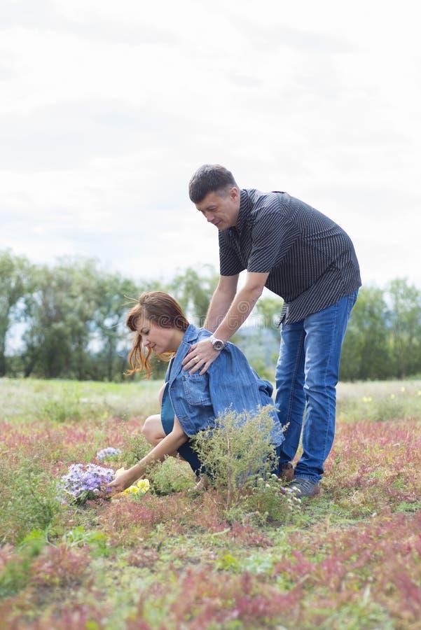 Liebhaber bemannen und Frauenweg auf Feld mit roten Blumen lizenzfreies stockbild
