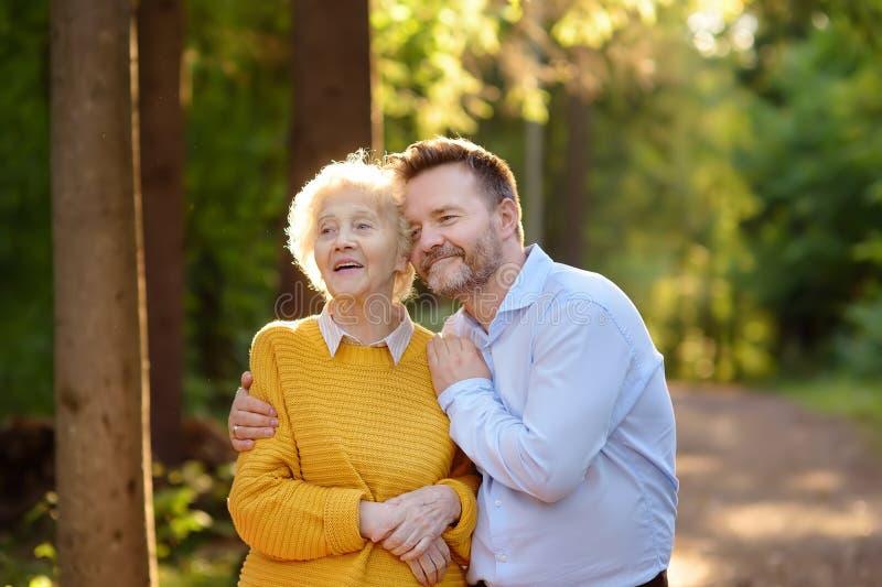 Liebhaber des erwachsenen Sohnes, der seine glückliche ältere Mutter während des Spaziergangs im Sommerpark empfängt stockfoto
