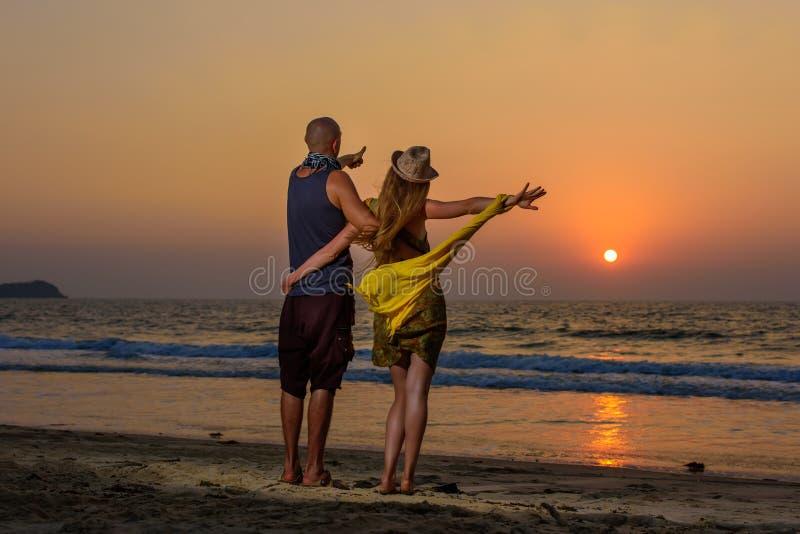 Liebhaber, die gegen Sonnenuntergang auf dem Meer umarmen Junge Paarstellung auf einem Strand und Bewundern zum Sonnenuntergang lizenzfreies stockfoto