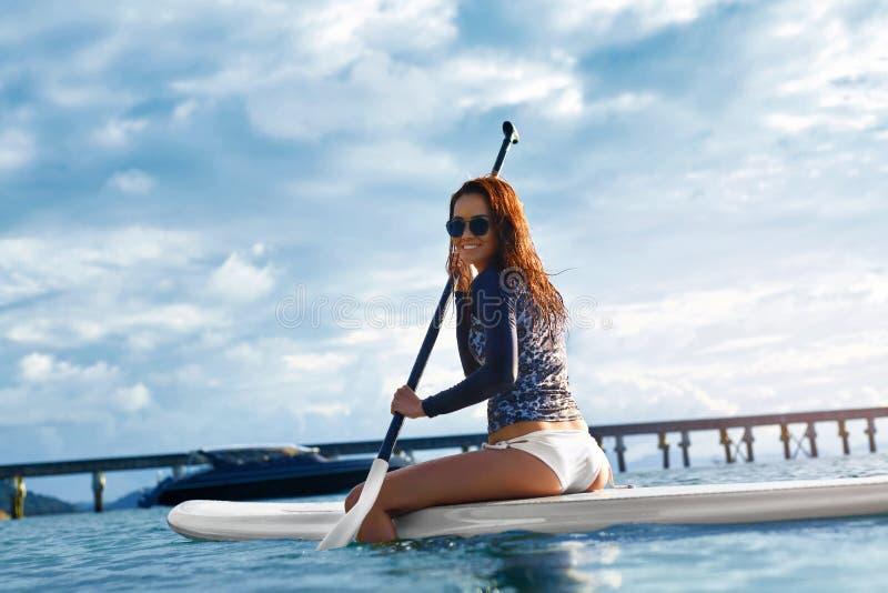 liebhaberei Mädchen, das auf Surfbrett schaufelt Junge Frau auf dem Strand von Formentera-Insel lizenzfreies stockbild