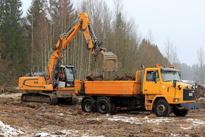 Liebherr-Kettenbagger Loads Sisu Truck lizenzfreie stockbilder