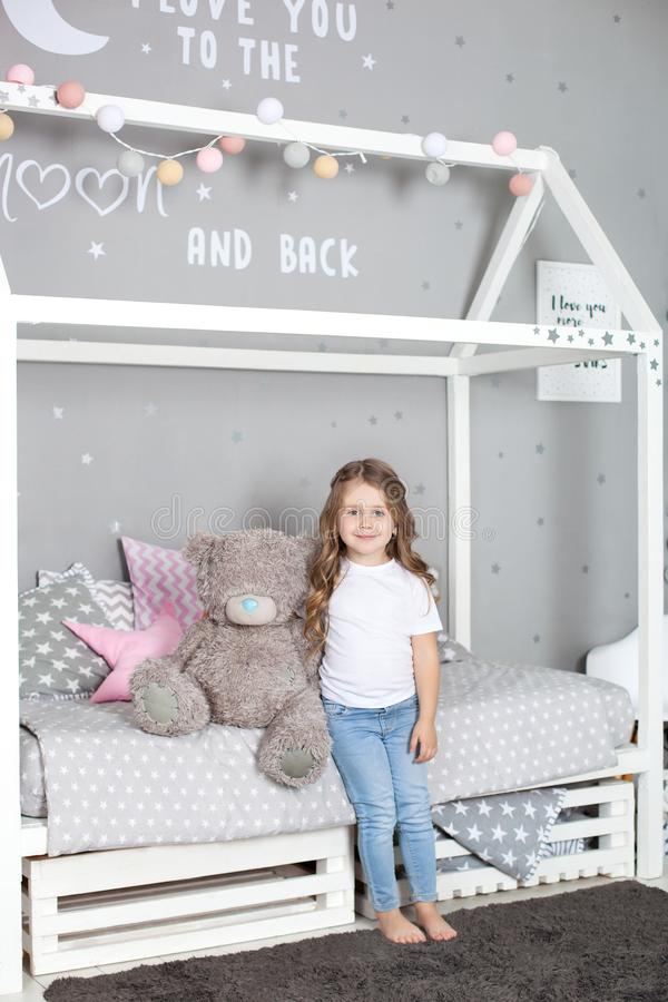 Lieblingsspielzeug M?dchenkind sitzen auf Bettumarmungsteddyb?ren in ihrem Schlafzimmer Kind bereiten vor sich schlafen zu gehen  lizenzfreies stockfoto