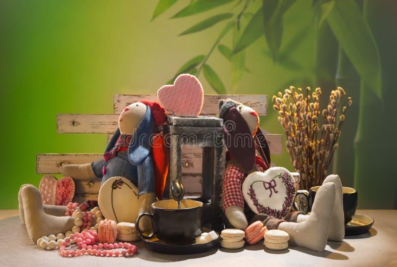 Liebres suaves de las muñecas en los pares del amor, té en tazas, imagenes de archivo