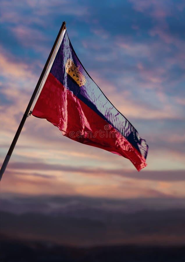 Liechtenstein flag waving on sky at dusk stock photo