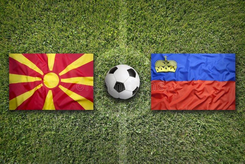 Liechtenstein versus De vlaggen van Macedonië op voetbalgebied stock foto's