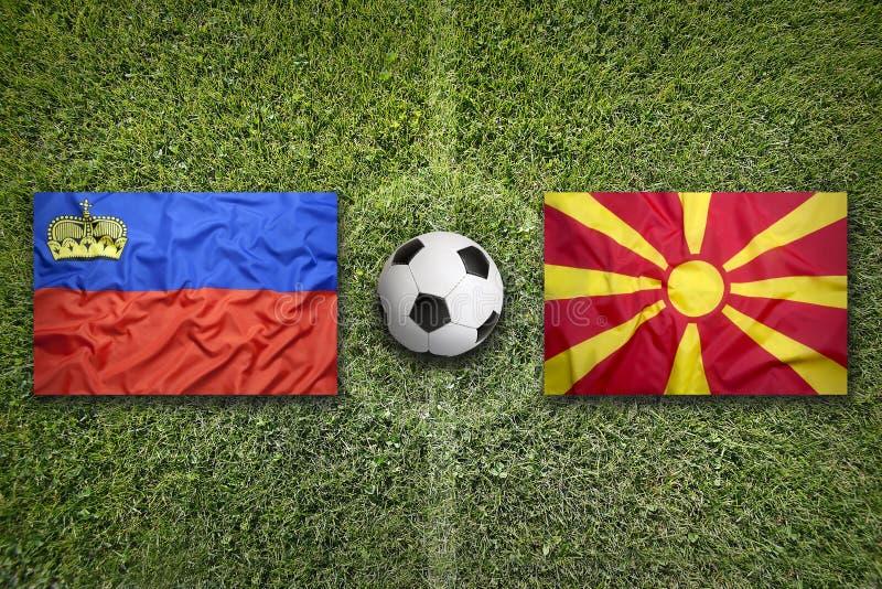 Liechtenstein vs. Macedonia flags on soccer field royalty free stock photos