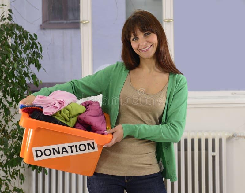 Liefdadigheid: Vrouw met de doos van de kledingsschenking stock afbeeldingen