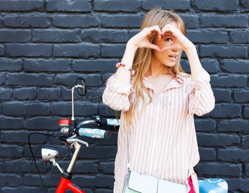 Liefde Close-upportret die gelukkige jonge vrouw met lang blon haar glimlachen, die hart maken ondertekenen, symbool met handen p stock afbeeldingen