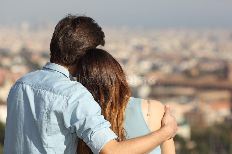 In liefde dateren en paar die lettend op de stad koesteren stock afbeelding