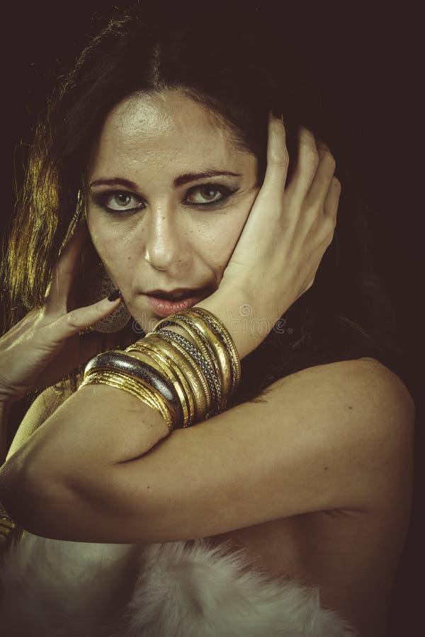 Liefde, donkerbruine vrouw die wit bont en gouden juwelen dragen royalty-vrije stock foto's