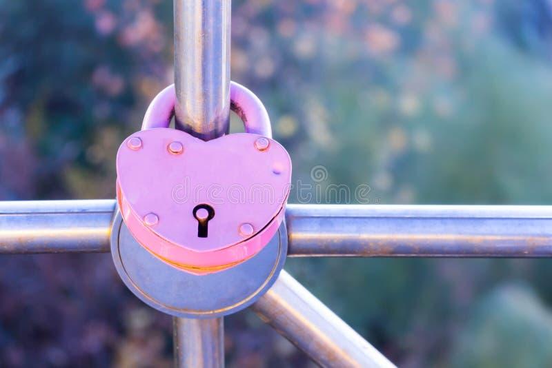 Liefde Een hart Het slot is strak gesloten op de leuning als teken van eeuwige liefde De dag van de valentijnskaart royalty-vrije stock foto