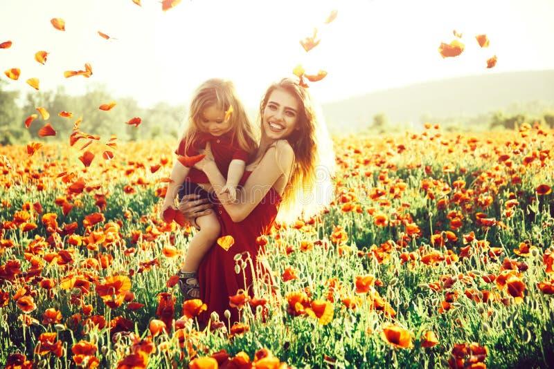 Liefde en familie, gelukkig moeder en kind op papavergebied royalty-vrije stock afbeeldingen