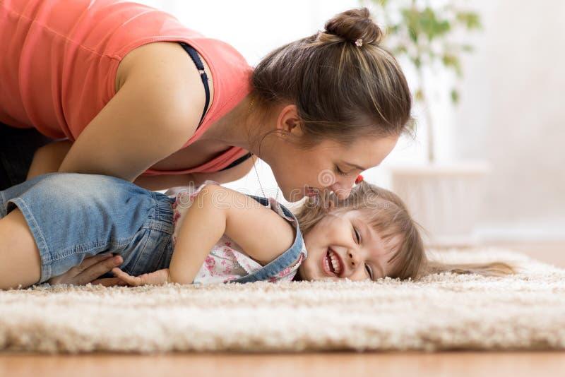 Liefde en familiemensenconcept - gelukkige mamma en kinddochter die een pret hebben thuis royalty-vrije stock foto