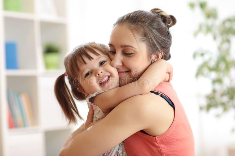 Liefde en familiemensenconcept - gelukkige moeder en kinddochter die thuis koesteren stock foto