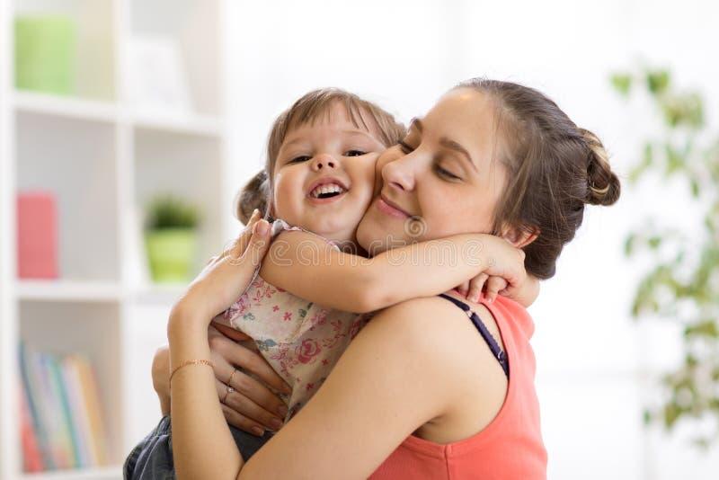 Liefde en familiemensenconcept - gelukkige moeder en kinddochter die thuis koesteren royalty-vrije stock foto