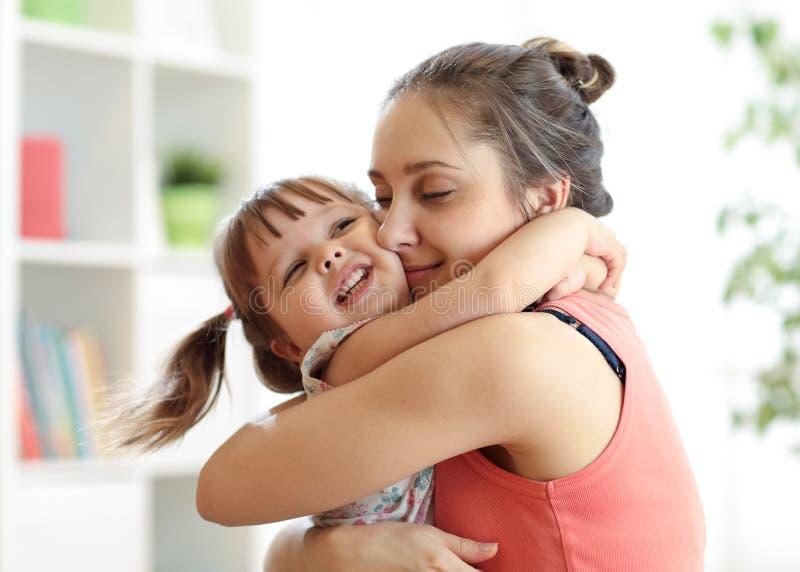 Liefde en familiemensenconcept - gelukkige moeder en kinddochter die thuis koesteren royalty-vrije stock afbeeldingen