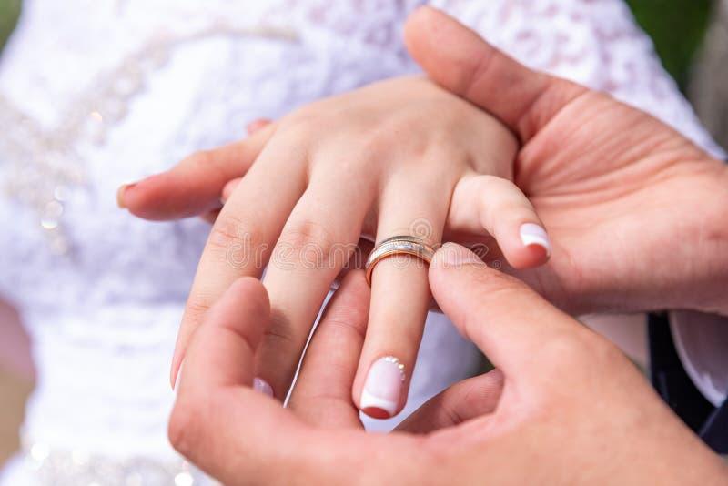 Liefde en huwelijk De ceremonie van het huwelijk Sluit omhoog van bruidegom die gouden ring op bride& x27 zetten; s vinger stock afbeelding