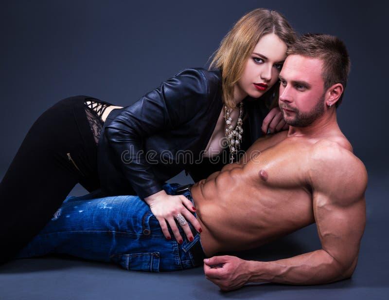 Liefde en seksualiteitconcept - sportief paar die over grijs liggen royalty-vrije stock foto