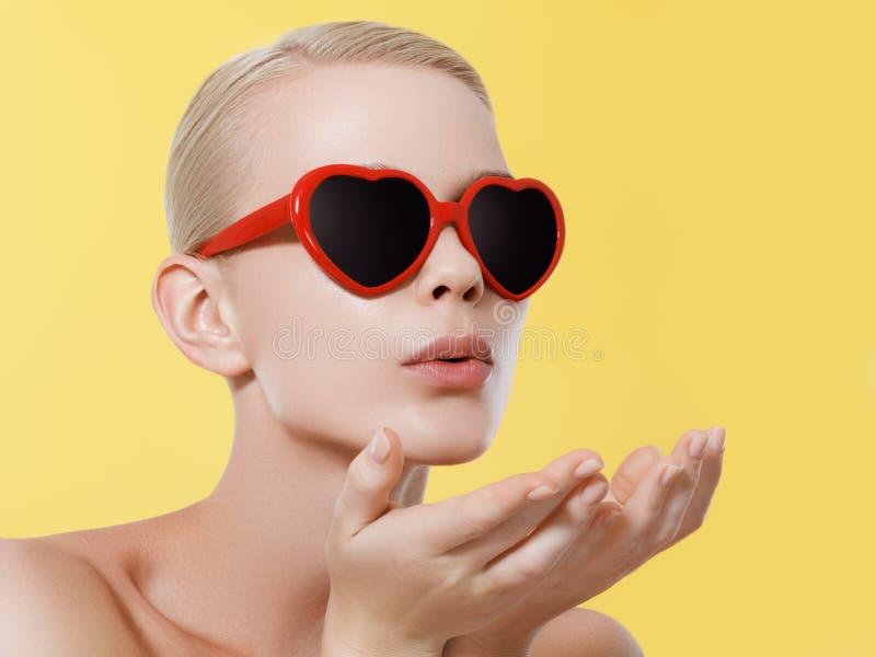 Liefde, geluk, valentijnskaartendag, gezichtsuitdrukkingen en mensenconcept - portret van tiener in roze zonnebril met stock afbeeldingen