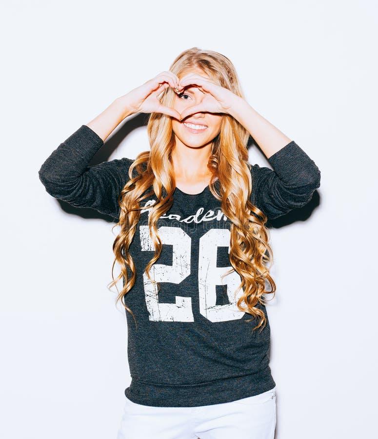 Liefde Portret die gelukkige jonge vrouw met lang blond haar glimlachen, die hart maken ondertekenen, symbool met achtergrond van royalty-vrije stock foto's