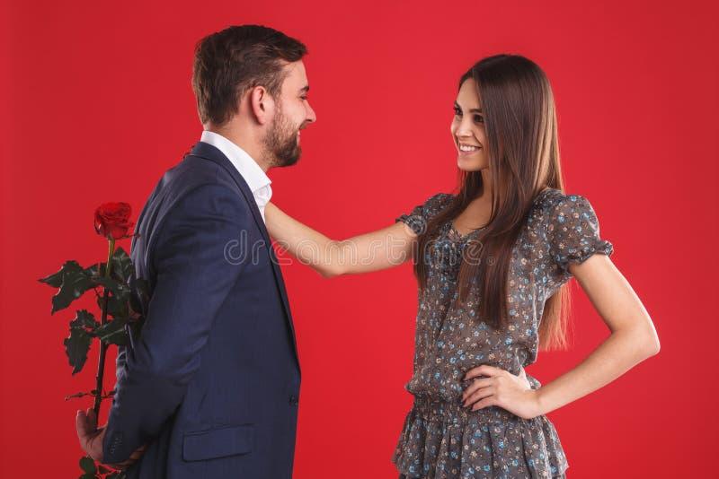 Liefde, Romaanse, valentijnskaartendag, paar en mensenconcept - gelukkige jonge man die rode bloem geven aan glimlachende vrouw royalty-vrije stock afbeeldingen