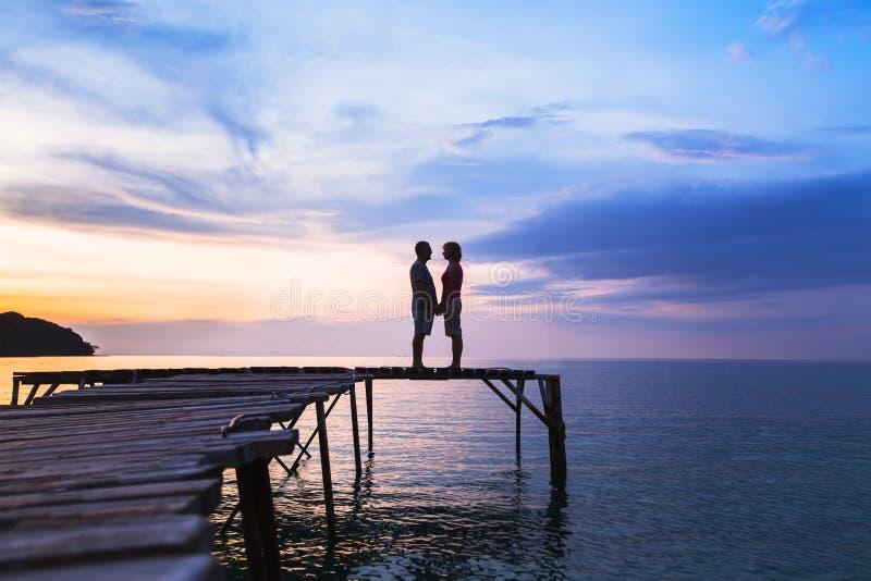 Liefde, silhouet van hartelijk paar op de pijler bij zonsondergangstrand royalty-vrije stock foto's