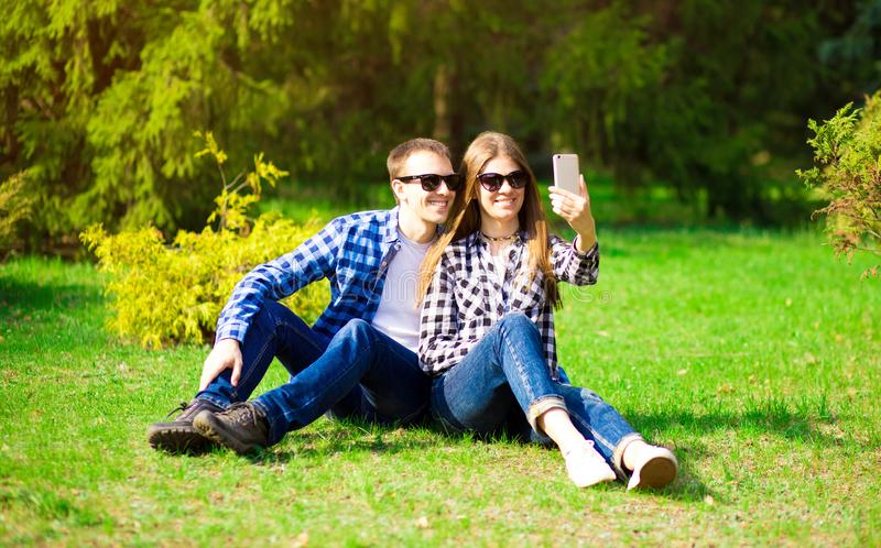 Liefde, technologie, verhoudings, familie en mensenconcept - gelukkig glimlachend jong paar die selfie in de zomerpark nemen royalty-vrije stock fotografie