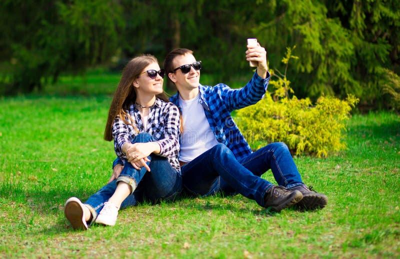 Liefde, technologie, verhoudings, familie en mensenconcept - gelukkig glimlachend jong paar die selfie in de zomerpark nemen royalty-vrije stock foto's