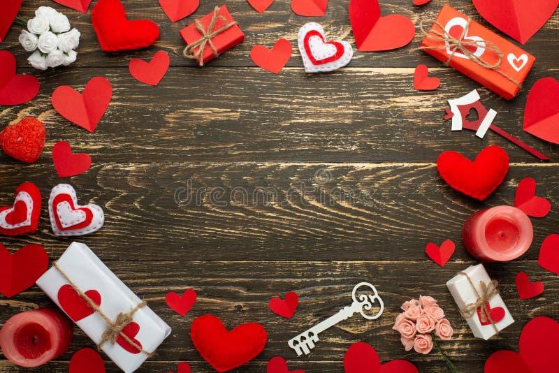 Liefde, textuur met rode harten, kaarsen, giften voor minnaars op een houten achtergrond De dag van de valentijnskaart `s Vlak-le royalty-vrije stock afbeelding