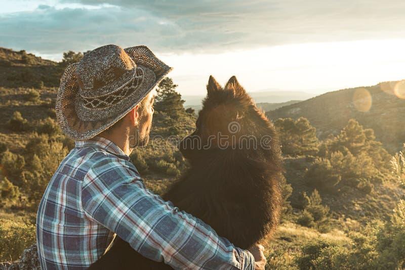 Liefde tussen een mens en een hond Gekoesterde kerel en hond stock afbeelding