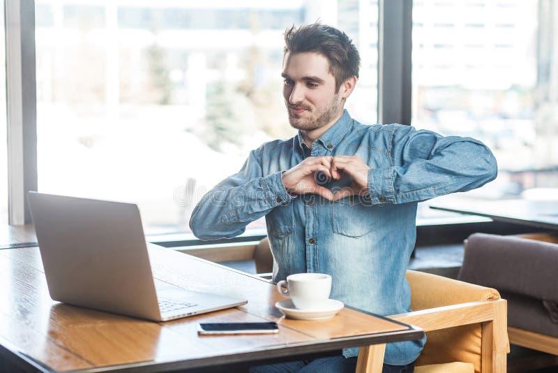 Liefde u! Het portret van romantische gelukkige jonge vriend in jeansoverhemd zit in koffie en toont zijn meisje een hart royalty-vrije stock fotografie