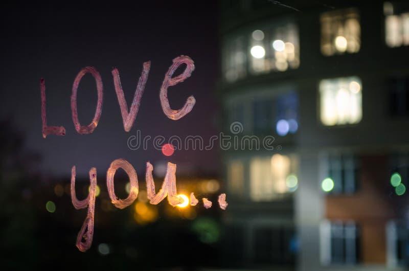 Liefde u, inschrijvingstekst door lippenstift op het vensterglas in de nacht Het concept van de liefde stock fotografie