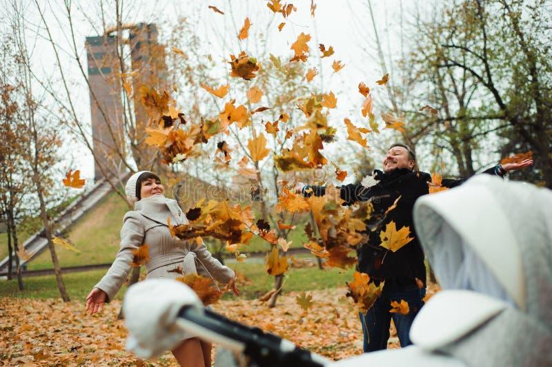Liefde, verhoudingen, seizoen en mensenconcept - gelukkig jong paar die de herfstbladeren omhoog in park werpen royalty-vrije stock afbeelding