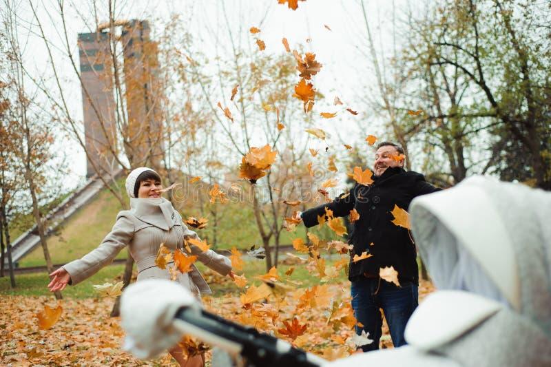 Liefde, verhoudingen, seizoen en mensenconcept - gelukkig jong paar die de herfstbladeren omhoog in park werpen stock foto