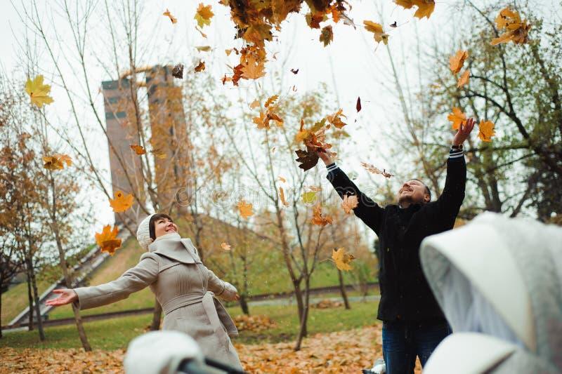 Liefde, verhoudingen, seizoen en mensenconcept - gelukkig jong paar die de herfstbladeren omhoog in park werpen stock fotografie