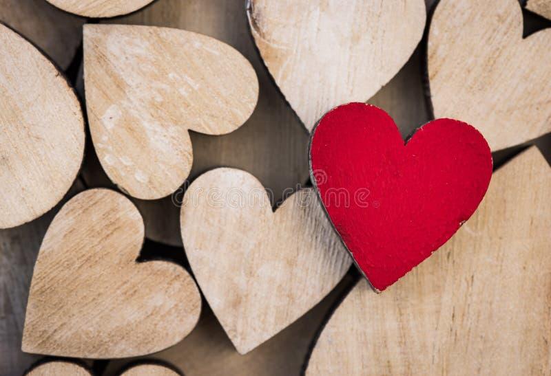 Liefdeachtergrond met rood hart tussen vele houten harten, close-up stock afbeeldingen