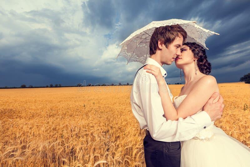 In liefdebruid en bruidegom op tarwegebied met blauwe hemel in de rug royalty-vrije stock afbeelding