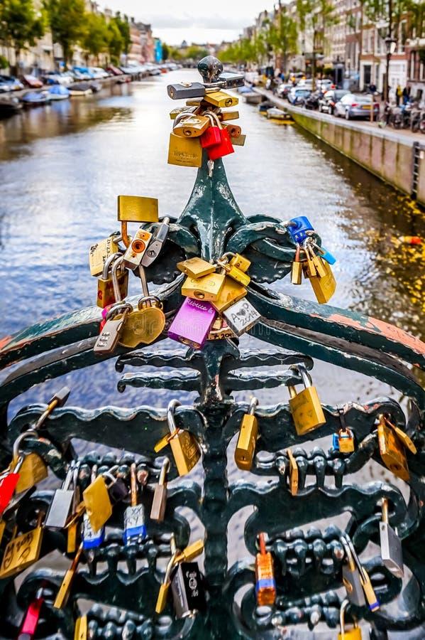 Liefdehangsloten op een traliewerk van een brug over Keizersgracht in het oude stadscentrum van Amsterdam stock foto