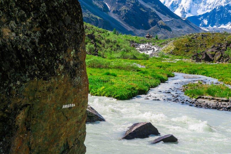 Liefdeinschrijving op de steen Akkemrivier en bergenmening r royalty-vrije stock foto
