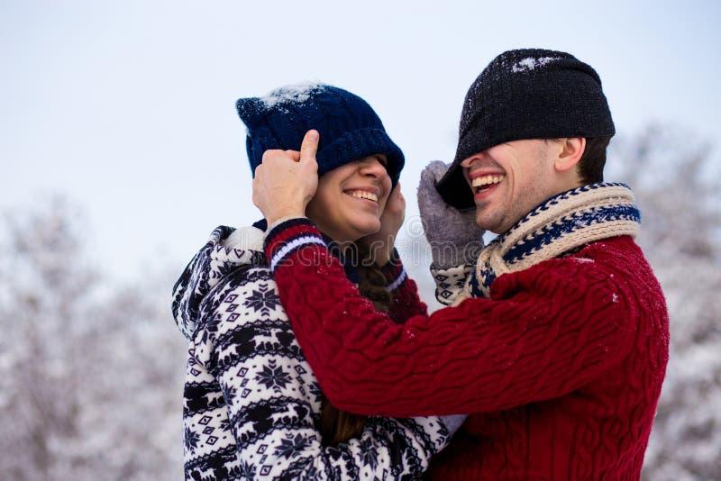 Liefdepaar die in heldere kleren in openlucht in de winter spelen royalty-vrije stock afbeeldingen
