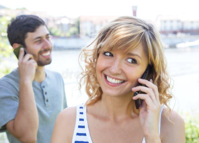 Liefdepaar die op telefoon spreken stock foto