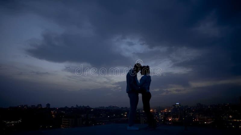 Liefdepaar die van romantische ogenblikken op dak, verlichte stad bij nacht genieten stock foto