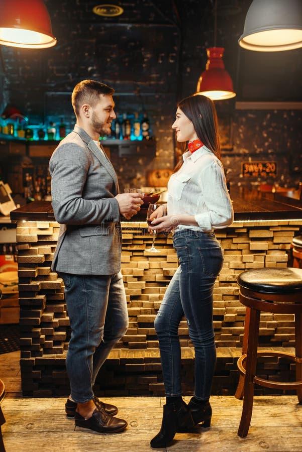 Liefdepaar die zich tegen barteller bevinden stock fotografie