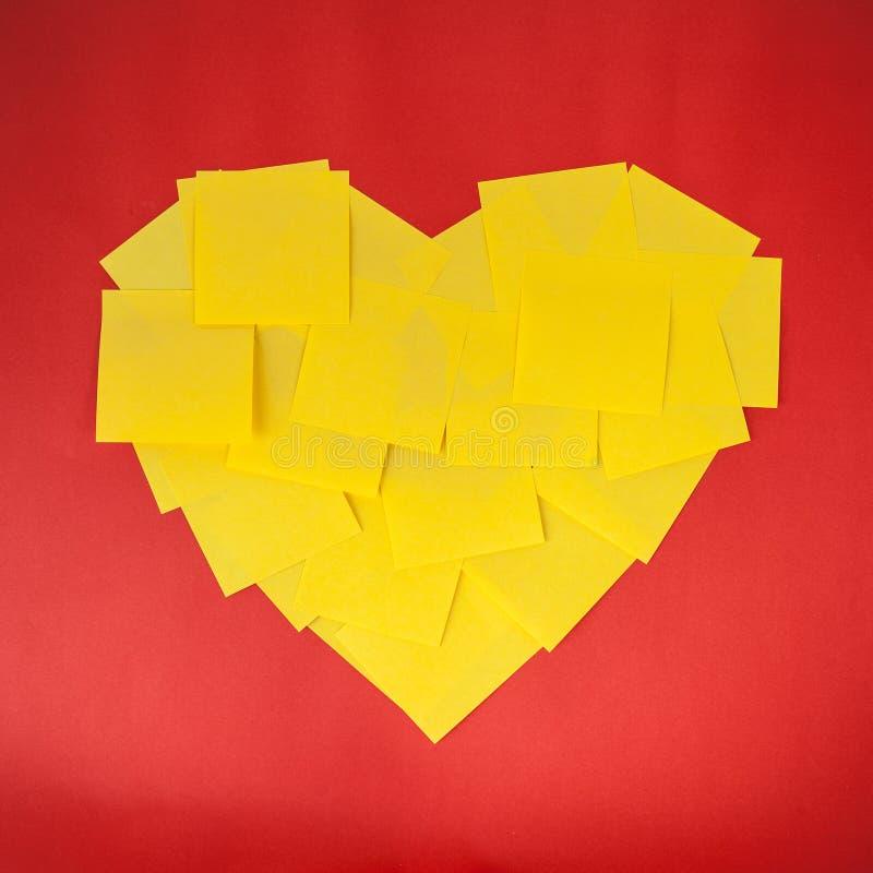 Liefdevorm door gele nota's over rode document achtergrond stock foto's
